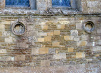 Part of the west wall showing two of the roundels and some of the arch stones re-used in its construction.